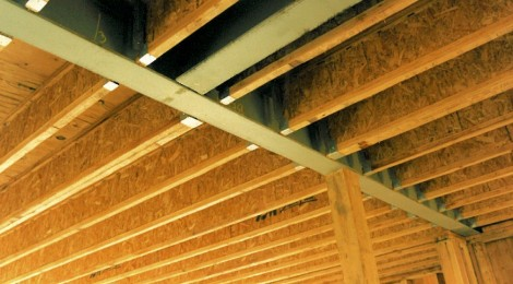 Construction phase - steel i-beams recessed in ceiling to pick up point loads from above custom homes by Rick Bernard.